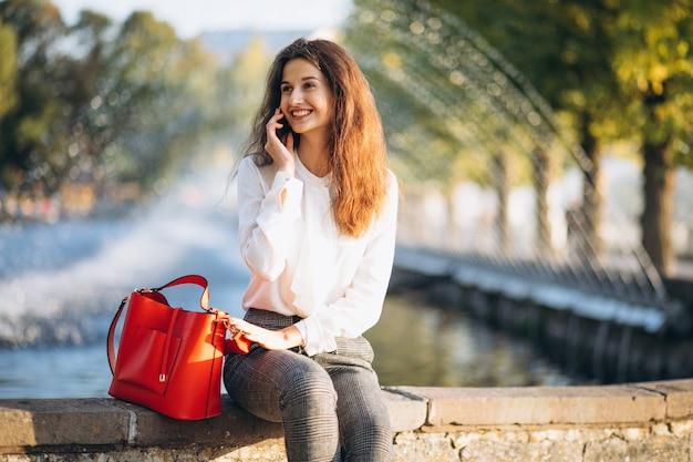 Junge geschäftsfrau, die telefon im park zur mittagspause verwendet Kostenlose Fotos