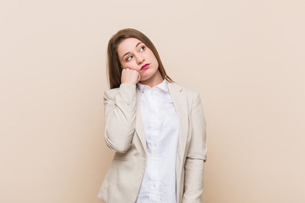 Junge geschäftsfrau, die traurig und nachdenklich sich fühlt und kopie betrachtet. Premium Fotos