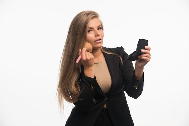 Junge geschäftsfrau im schwarzen anzug, der make-up auf ihre wange aufträgt. Kostenlose Fotos