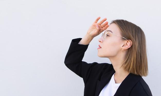 Junge geschäftsfrau in brille und einer schwarzen jacke schaut seitlich auf weiß Premium Fotos