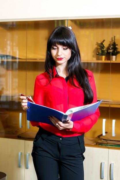 Junge geschäftsfrau in der roten bluse mit einem ordner von dokumenten im büro Premium Fotos