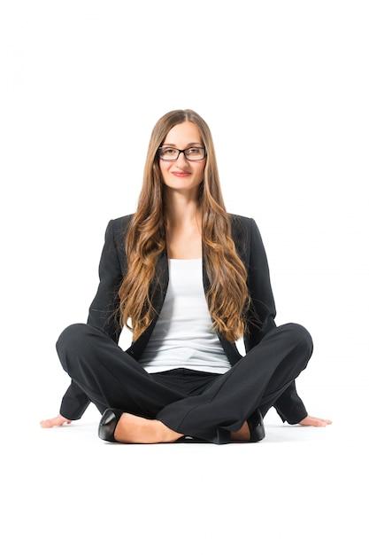 Junge geschäftsfrau mit den gläsern, die auf fußboden sitzen Premium Fotos