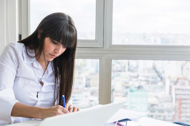 Junge geschäftsfrau mit laptop auf dem schreibtisch, der im büro arbeitet Kostenlose Fotos
