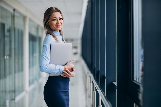 Junge geschäftsfrau mit laptop, der in einem büro steht Kostenlose Fotos