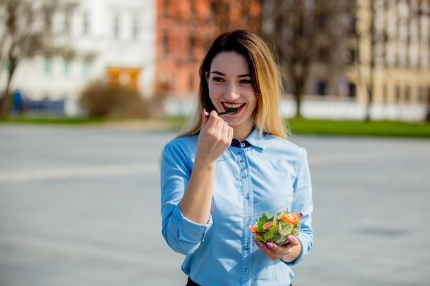 Junge geschäftsfrau mit salatbrotdose auf im freien Premium Fotos