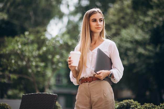 Junge geschäftsfrau mit trinkendem kaffee des laptops außerhalb des cafés Kostenlose Fotos