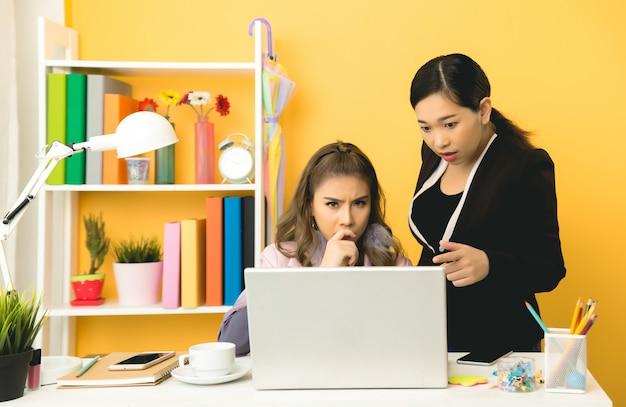 Junge geschäftsfrauen, die im büro plaudernd sprechen Kostenlose Fotos