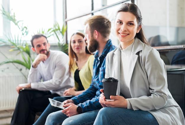 Junge geschäftskollegen, die zusammen während der pause im büro sitzen Kostenlose Fotos