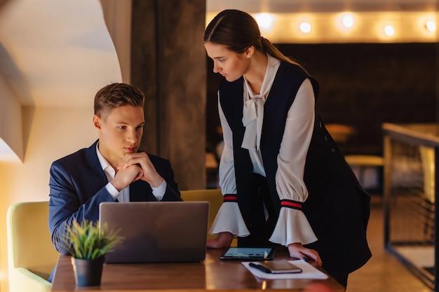 Junge geschäftsmänner junge und mädchen arbeiten mit einem laptop, einer tablette und anmerkungen im café Premium Fotos