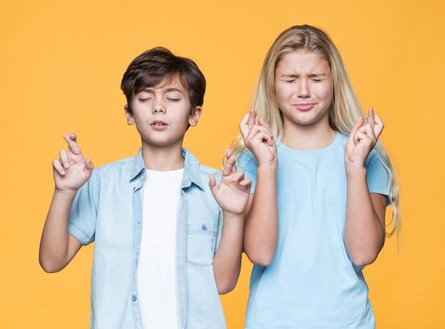Junge geschwister, die zusammen wünsche machen Kostenlose Fotos
