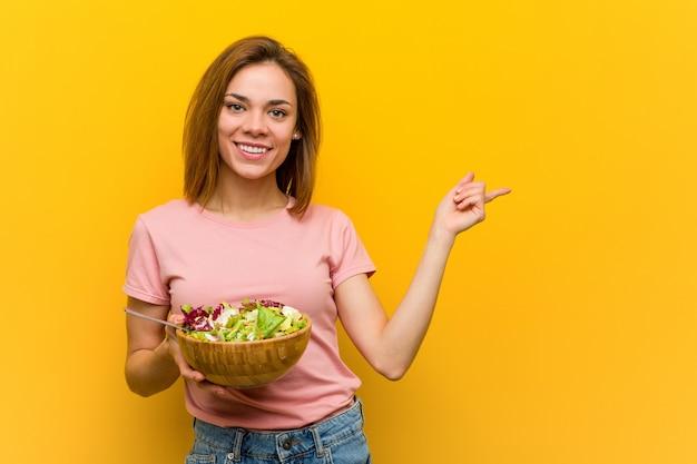 Junge gesunde frau, die ein salatlächeln freundlich zeigt mit dem zeigefinger weg hält. Premium Fotos