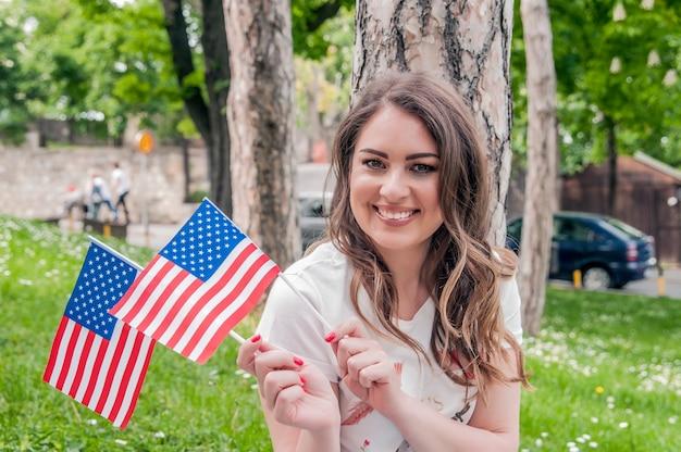 1b95ca38909 Junge glückliche Patriot Mädchen mit der amerikanischen Flagge am 4. Juli.  Land