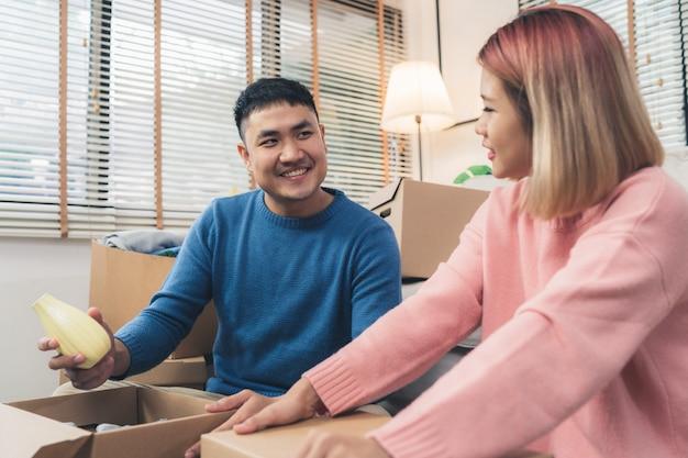Junge glückliche asiatische paare, die auf ihr neues haus, offene kästen umziehen, um alte gegenstände vom alten haus zu überprüfen Kostenlose Fotos