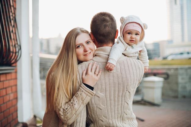 Junge glückliche familie, die zusammen lächelt und steht Premium Fotos