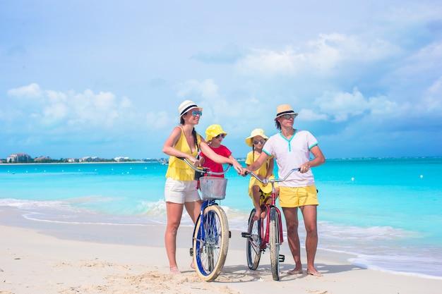 Junge glückliche familie fahrradfahren am tropischen strand Premium Fotos
