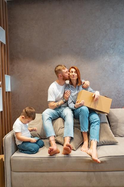 Junge glückliche familie mit dem kind, welches die kästen zusammen sitzen auf sofa auspackt Kostenlose Fotos