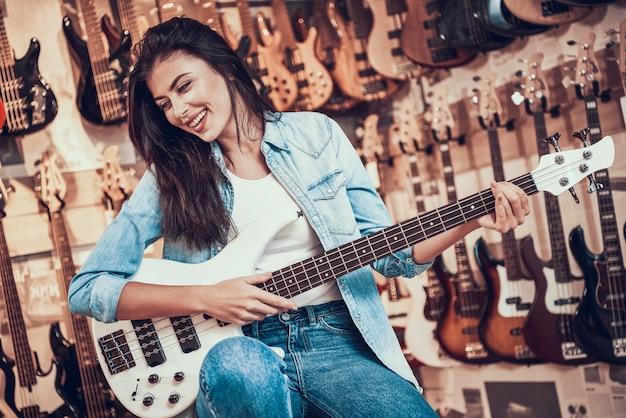 Junge glückliche frau, die e-gitarre im musikalischen speicher spielt Premium Fotos