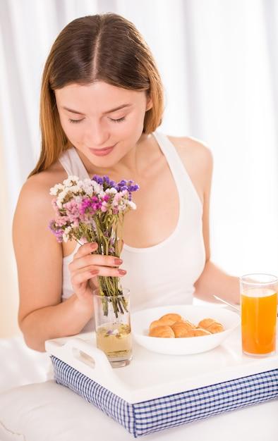 Junge glückliche frau, die frühstück in seinem schlafzimmer isst. Premium Fotos