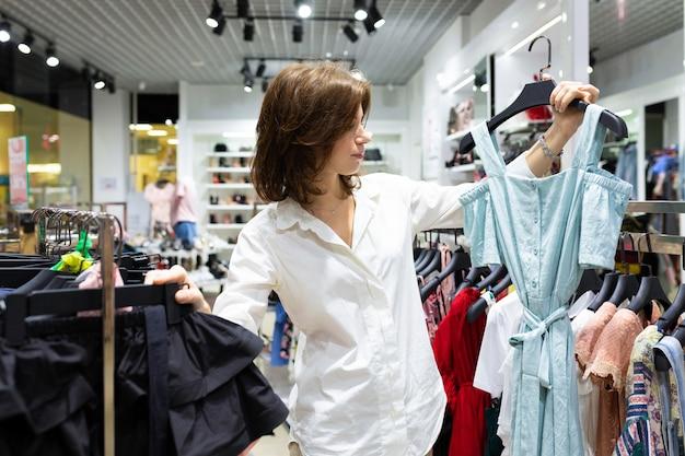 Junge glückliche frau, die hellblaues kleid im bekleidungsgeschäft hält Premium Fotos