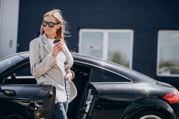 Junge glückliche frau, die kaffee durch das auto trinkt Kostenlose Fotos