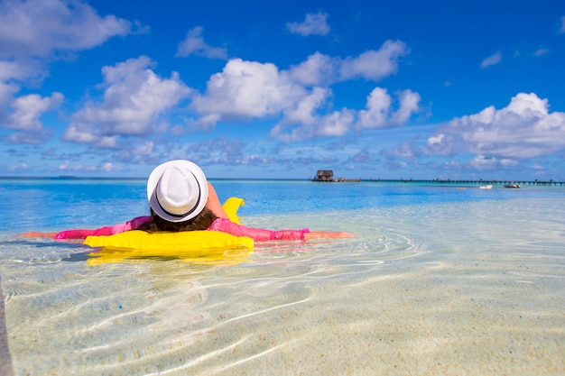 Junge glückliche frau, die mit luftmatratze im swimmingpool sich entspannt Premium Fotos