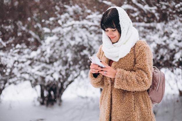 Junge glückliche frau in den warmen stoffen in einem winterpark Kostenlose Fotos