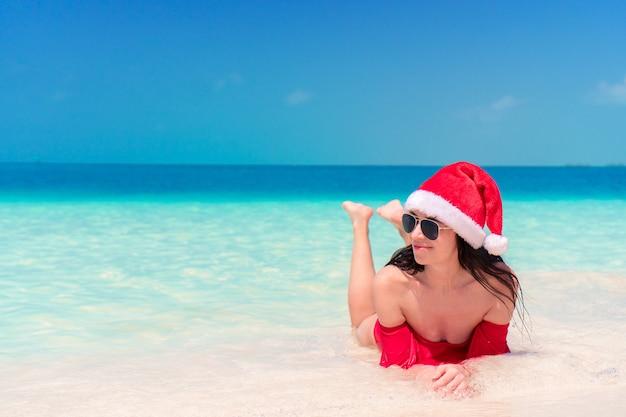 Junge glückliche frau in sankt-hut im badeanzug auf weißem strand an weihnachtsfeiertagen Premium Fotos