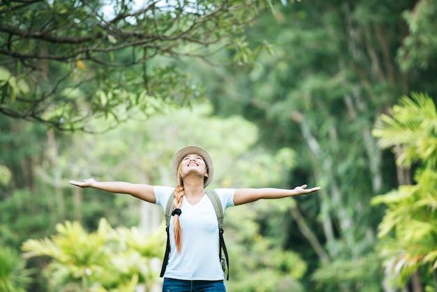 Junge glückliche frau mit dem rucksack, der hand anhebt, genießen mit natur. Kostenlose Fotos