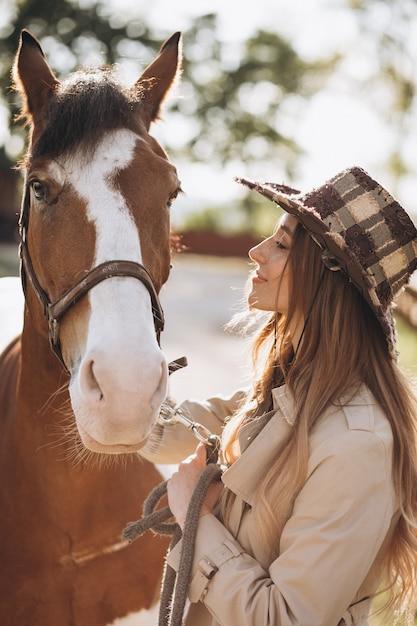 Junge glückliche frau mit pferd an der ranch | Kostenlose Foto