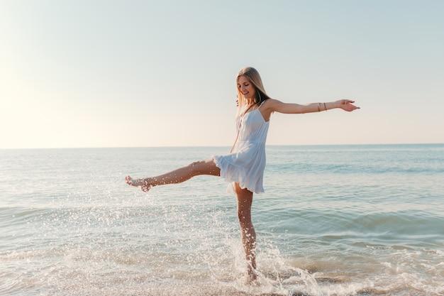Junge glückliche frau tanzt herum und dreht sich am sonnigen sommermode-stil des seestrandes im weißen kleid urlaub Kostenlose Fotos