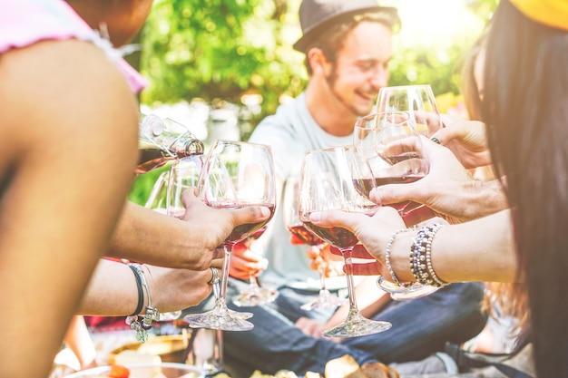 Junge glückliche freunde, die zusammen spaß in einem picknick am hinterhof zujubeln und haben Premium Fotos
