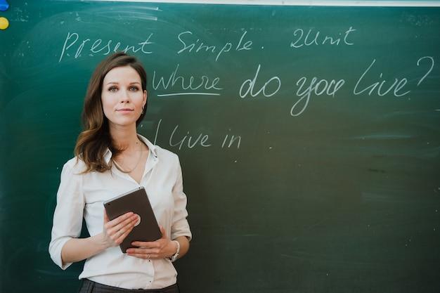 Junge glückliche lehrerin mit digitaler tablette im klassenzimmer. Premium Fotos