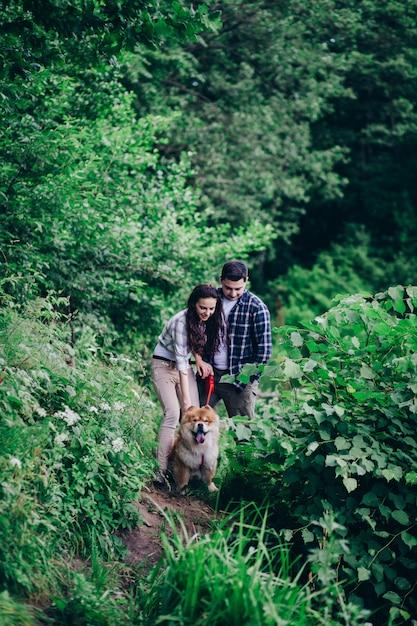Junge glückliche paare des mannes und der frau mit hund sitzen am rasen Premium Fotos