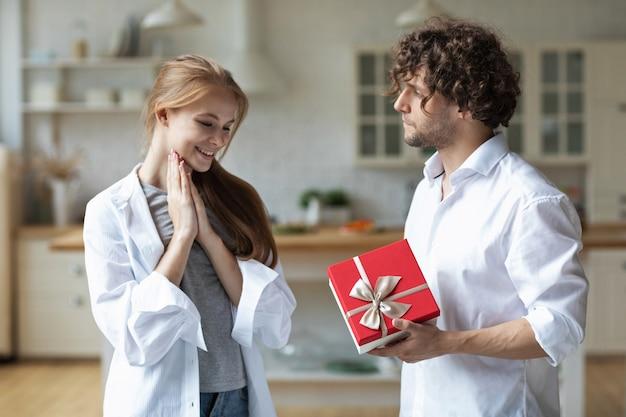 Junge glückliche paare zu hause geben sich gegenseitig geschenke Premium Fotos