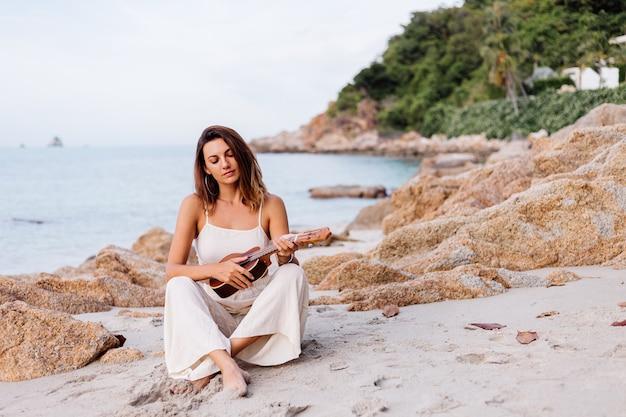 Junge glückliche ruhige kaukasische frau mit ukulele am tropischen felsigen strand bei sonnenuntergang Kostenlose Fotos