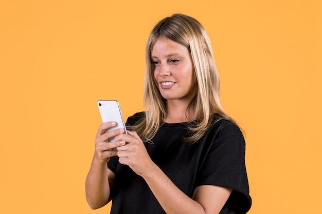 Junge glückliche sperrungsfrau, die handy auf gelbem hintergrund verwendet Kostenlose Fotos