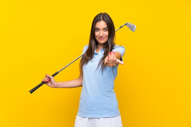 Junge golfspielerfrau, die einlädt, mit der hand zu kommen. schön, dass sie gekommen sind Premium Fotos