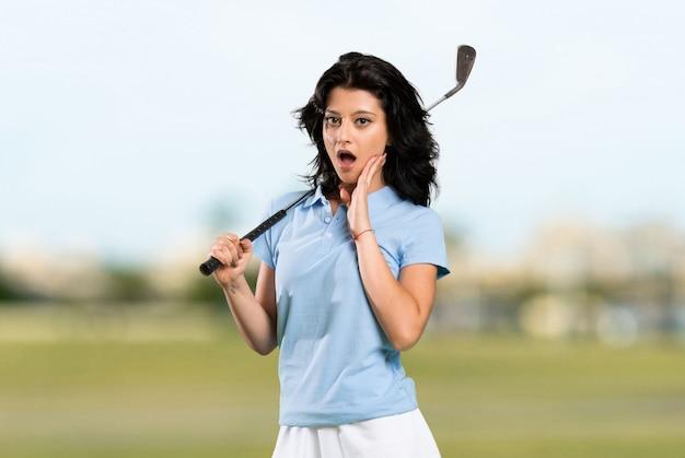 Junge golfspielerfrau mit überraschung und entsetztem gesichtsausdruck an draußen Premium Fotos