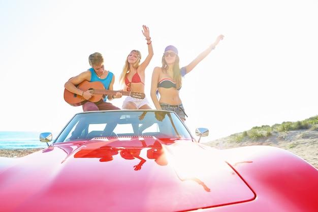Junge gruppe, die spaß am strand spielt gitarre spielen Premium Fotos