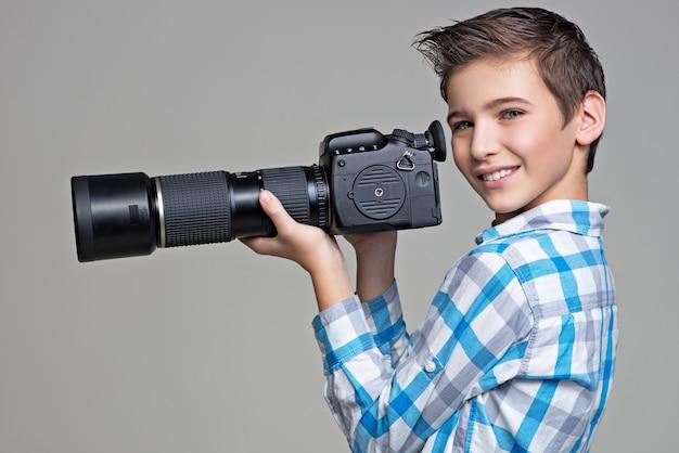 Junge hält große fotokamera mit teleobjektiven Kostenlose Fotos