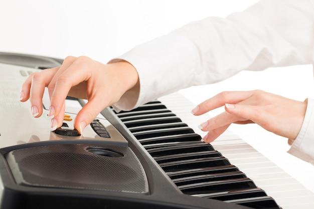 Junge hände der frau, die synthesizer lokalisiert auf weiß spielt Premium Fotos