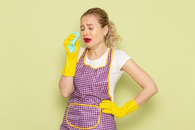 Junge hausfrau im hemd und im lila umhang mit gelben handschuhen, die grünen lappen halten, der auf grün weint Kostenlose Fotos