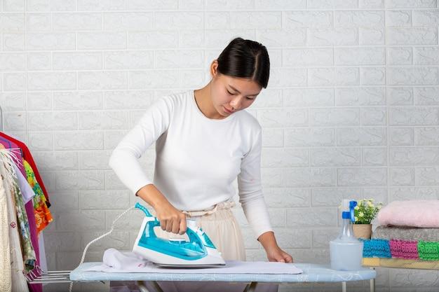 Junge hausfrauen, die bügeleisen benutzen, die seine kleidung auf einem weißen ziegelstein bügeln. Kostenlose Fotos