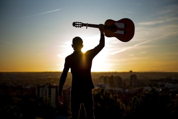 Junge hebt die gitarre in der stadt von madrid, spanien im hintergrund auf. Premium Fotos