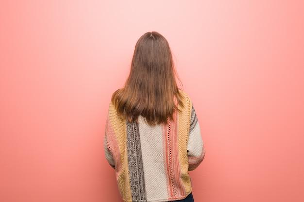 Junge hippiefrau auf dem rosa von hinten, zurück schauend Premium Fotos