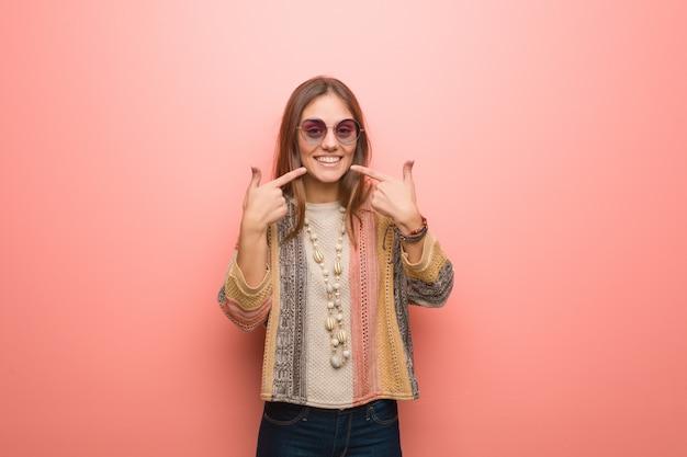 Junge hippiefrau auf rosa hintergrund lächelt und zeigt mund Premium Fotos