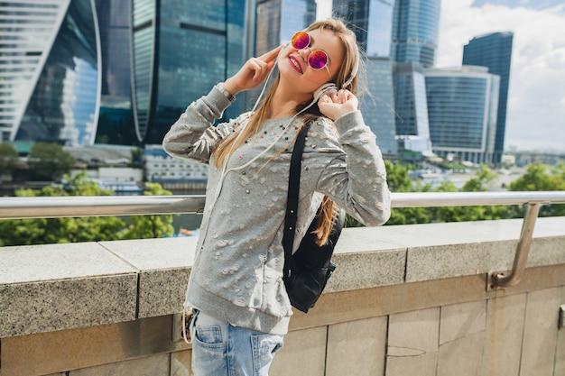 Junge hipster-frau, die spaß in der straße hat, die musik auf kopfhörern hört, rosa sonnenbrille tragend Kostenlose Fotos