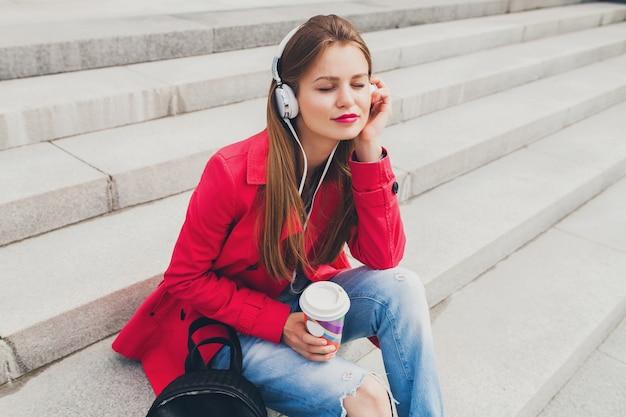 Junge hipster-frau im rosa mantel, jeans, die in der straße mit rucksack und kaffee sitzen musik auf kopfhörern hören Kostenlose Fotos