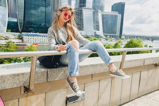Junge hipsterfrau, die spaß in der straße hat, die musik auf kopfhörern hört Kostenlose Fotos