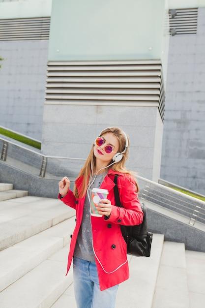 Junge hipsterfrau im rosa mantel, jeans in der straße mit rucksack und kaffee, die musik auf kopfhörern hören Kostenlose Fotos